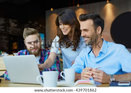 Business meeting at cafe - happy people working with laptop - stock photo