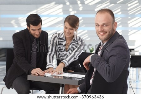 Business meeting at coffee table, happy business people working together.