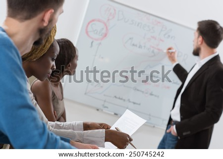 Business meeting at office. Handsome man presenting charts on whiteboard to team. Multi ethnic group of people - stock photo