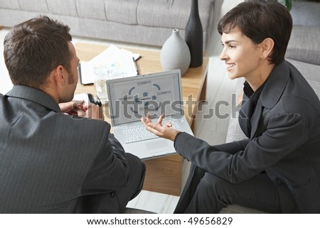 Business meeting at office. Youing businsspeople sitting on sofa, discussing charts on laptop screen. Overhead view. - stock photo