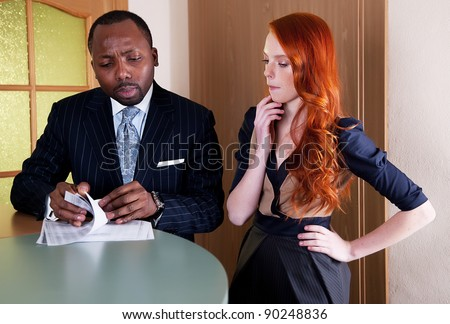 Business meeting between redhead woman and black man in office space
