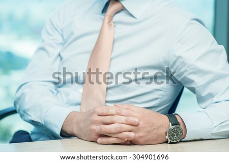 Business meeting. Confident businessman sitting at the table at the meeting. Close-up view of the hands of successful businessmen. Businessman showing hand gestures