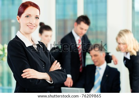 Business - meeting in an office; a colleague is looking into the camera - stock photo