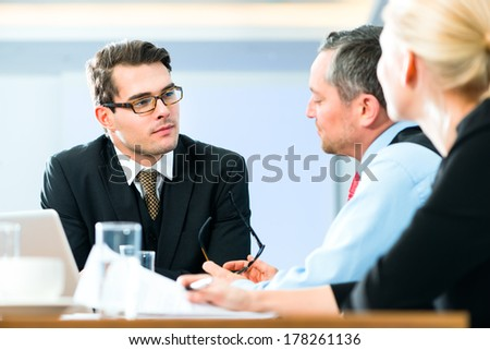 Business - meeting in office, the businesspeople with boss and team are discussing a document on Laptop computer - stock photo