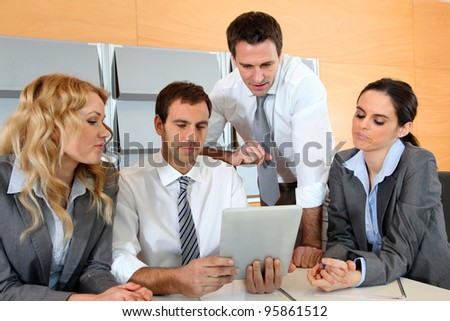 Business meeting in office with electronic tablet - stock photo