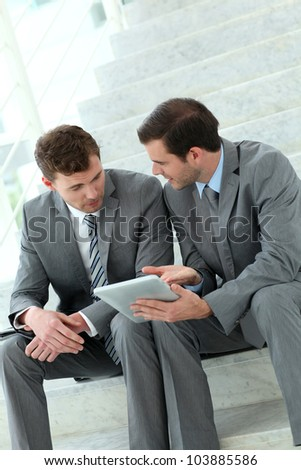 Business meeting in stairs with electronic tablet - stock photo