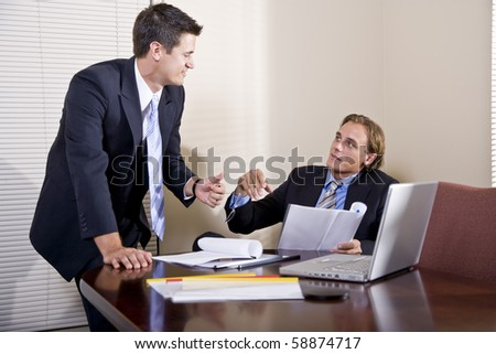 Business meeting - two businessmen in suits working together in boardroom