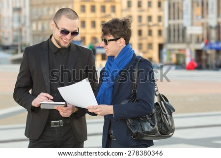 Business meeting. Two businesspeople looking at papers. Two modern business man discussing business documents and contracts in hand. Men in the business center on the background of an office building. - stock photo