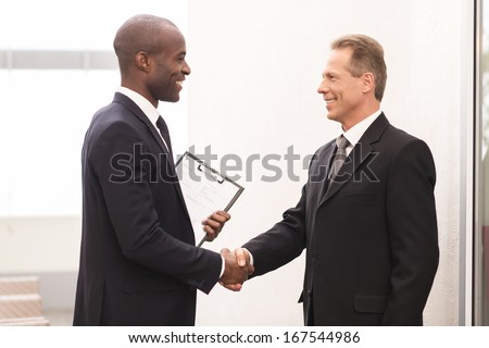 Business meeting. Two cheerful business men shaking hands and looking at each other - stock photo