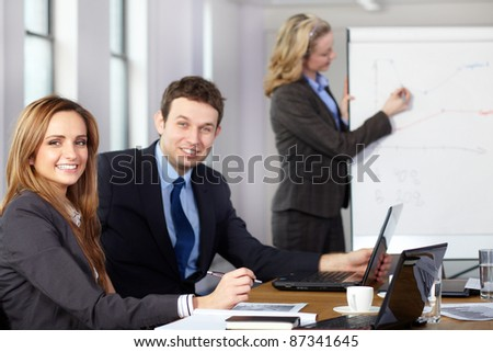 Business meeting, two colleagues on foreground while blonde female presents graph on flipchart on the background - stock photo