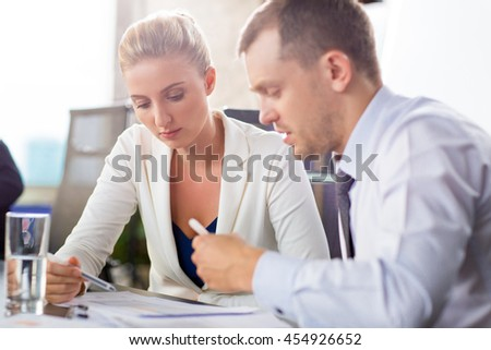 Business meeting. Two young business people sitting at desk in office and discussing something
