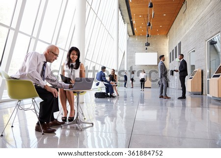 Business Meetings In Busy Office Foyer Area - stock photo