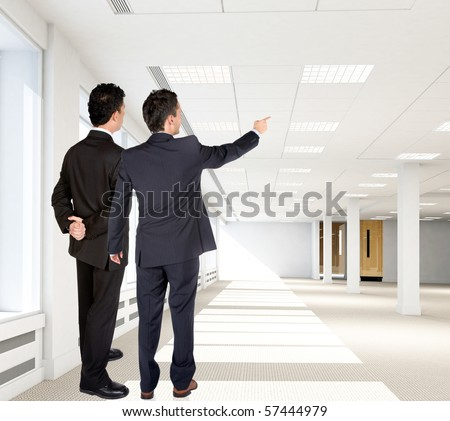 Business men at the new office pointing at something - stock photo