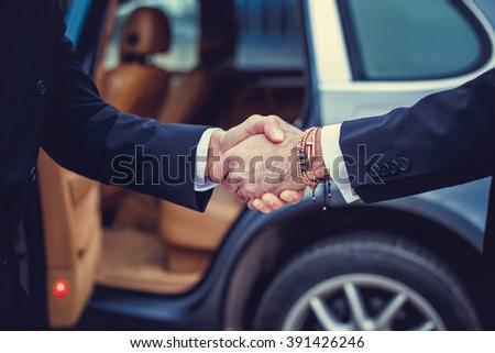Business men handshake near the car. - stock photo