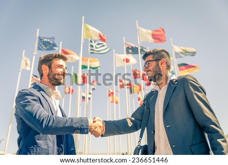 Business men handshake- Two businessmen walking and talking outdoors - stock photo