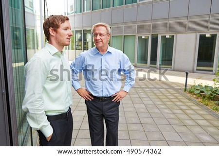Business men talking to each other during lunch break outside the office
