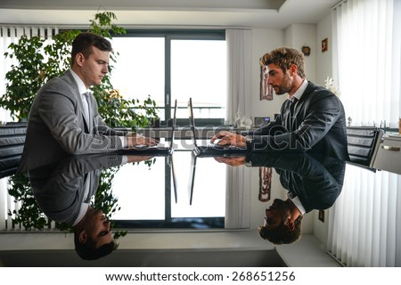 Business men working on computer desk - Busy office workers computing on lap top - Two men sitting at computer desk in front of each others - stock photo