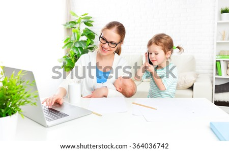 business  mother works at home via the Internet with their young children - stock photo