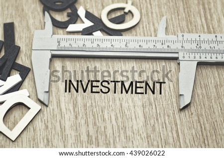Business motivation and finance concept, vernier caliper with word INVESTMENT over wooden floor and alphabetical word made from wood background - stock photo