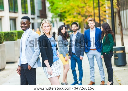 Business multiracial couple looking at camera, with four more people on background. They all are young, smiling and wearing smart casual clothes. Mixed race group. Teamwork and business concepts.