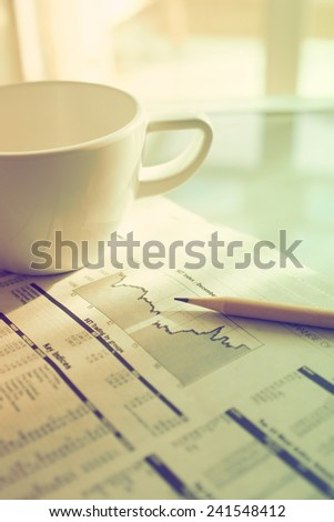 Business newspaper and coffee in vintage color toned style - stock photo