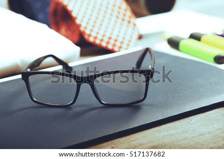 Business objects on the desk,including digital tablet, shirt, ties, lunch box, paper and pencils, top view
