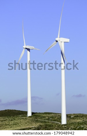 Business of wind energy. Turbines closeup with blue sky and green grass - stock photo