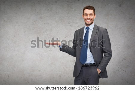 business, office, advertising and people concept - friendly young buisnessman showing something on the palm of his hand - stock photo