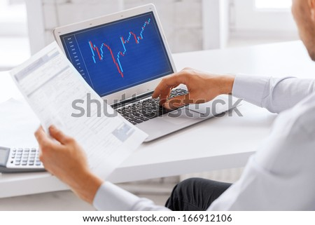 business, office and money concept - businessman working with forex chart and papers in office - stock photo