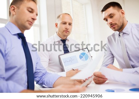 business, office and people concept - serious businessmen with papers in office - stock photo