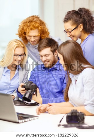 business, office and startup concept - smiling creative team with laptop computer and photocamers working in office