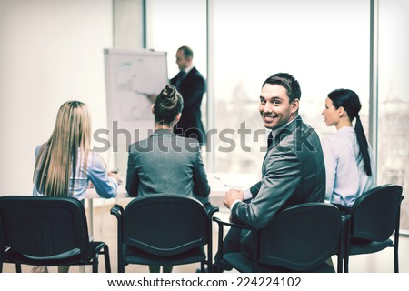 business, office and success concept - confident businessman with team in office - stock photo