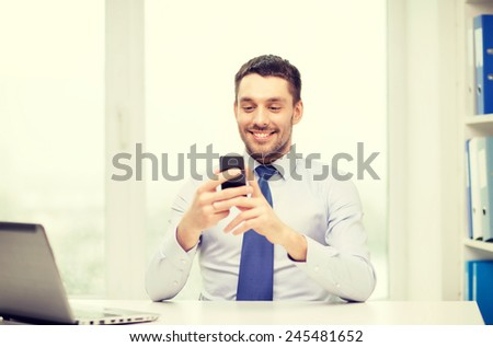 business, office and technology concept - smiling businessman with laptop computer and smartphone at office - stock photo