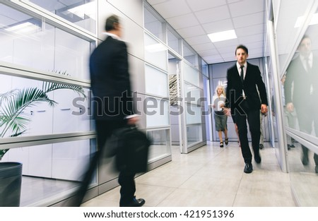 Business office daily life. Blurred people walking in an office corridor