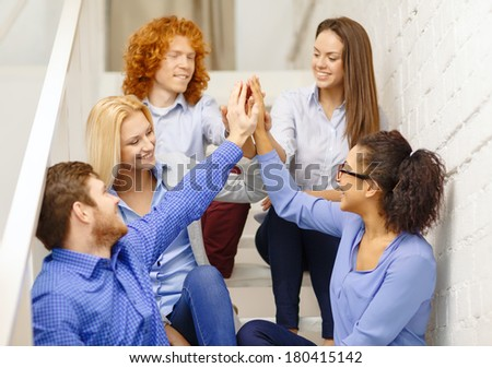 business, office, gesture and startup concept - smiling creative team doing high five gesture sitting on staircase - stock photo