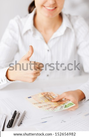 business, office, household, banking, tax, gambling concept - woman hands with euro cash money and thumbs up - stock photo