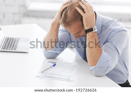 business, office, school and education concept - stressed businessman with papers at work - stock photo