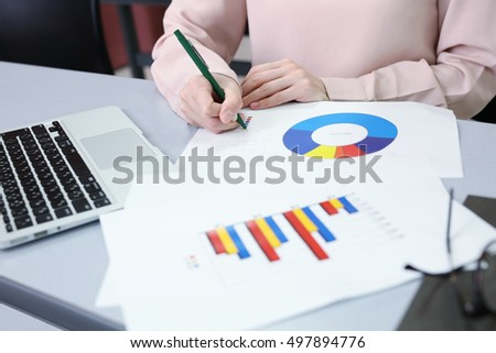 business, office, tax, school and education concept - Female hand hold green pen while working with graph at workplace.