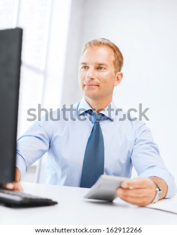 business, office, tax, school and education concept - smiling businessman with calculator, computer and papers - stock photo