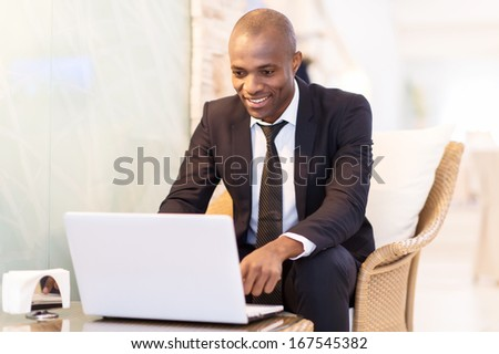 Business on the go. Cheerful young African businessman using his laptop while sitting at the restaurant  - stock photo