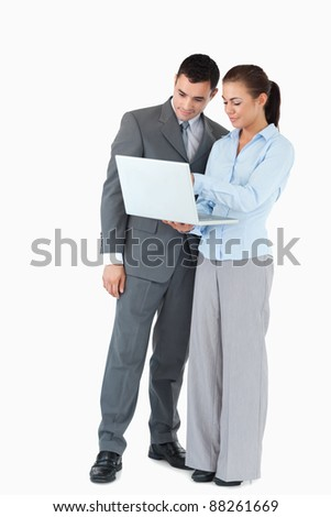 Business partner looking at a notebook together against a white background