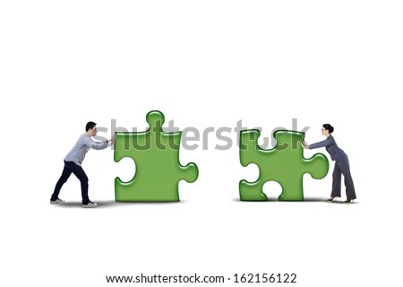 Business partner putting together two puzzle pieces - isolated on white background - stock photo