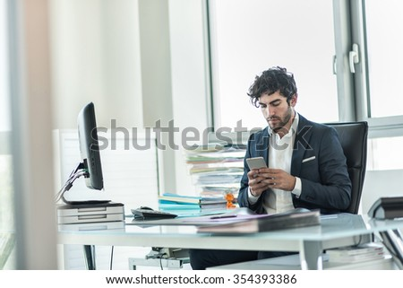 Business partner sitting at his tidy glass desk in front of his computer in a luminous white office. He has a beard and is wearing a dark suit with shirt. He is answering his emails on his smartphone.