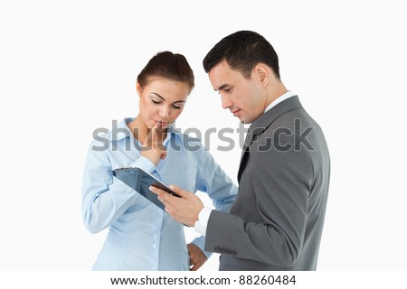 Business partners analyzing document on the clipboard against a white background - stock photo