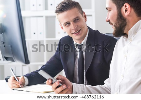 Business partners are having conversation in office. One is holding his cell phone. Second is writing in notebook. Concept of communication importance at work