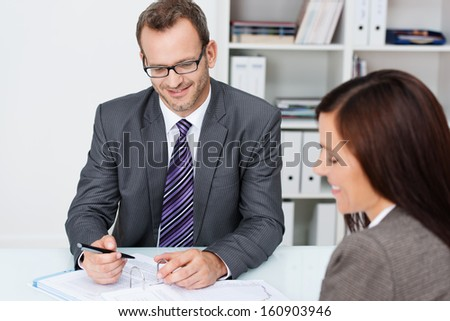 Business partners at work in the office with focus over the shoulder of a woman to a smiling confident businessman in glasses working on paperwork - stock photo
