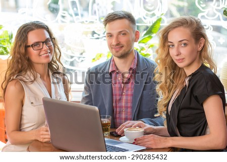 Business partners from advertising agencies having negotiations. People dicussing problems viewed onlaptop in cafe. - stock photo