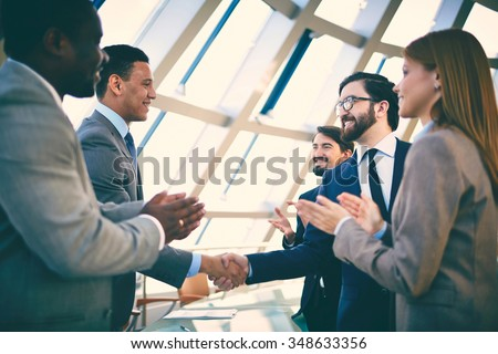 Business partners greeting each other after signing contract - stock photo