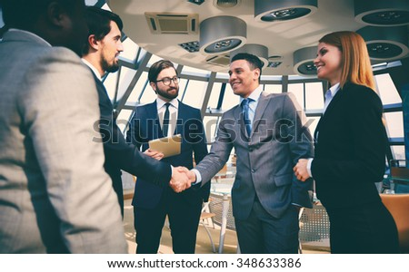 Business partners greeting one another by handshaking - stock photo