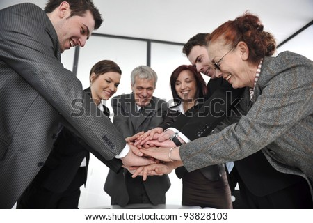 Business partners hands on top of each other symbolizing companionship and unity - stock photo